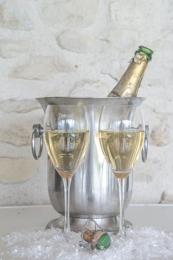 Celebration concept: vintage bottle of champagne in the bucket, two champagne glasses and cork. Two glasses of champagne and vintage bottle in the bucket stock photography