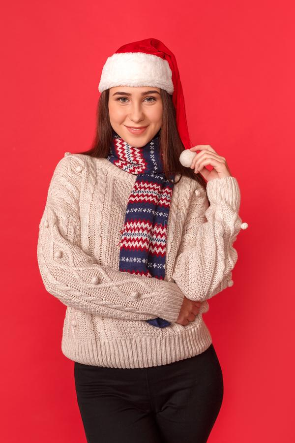 Celebration Concept. Young woman in scarf and santa hat standing isolated on red posing to camera confident stock photo