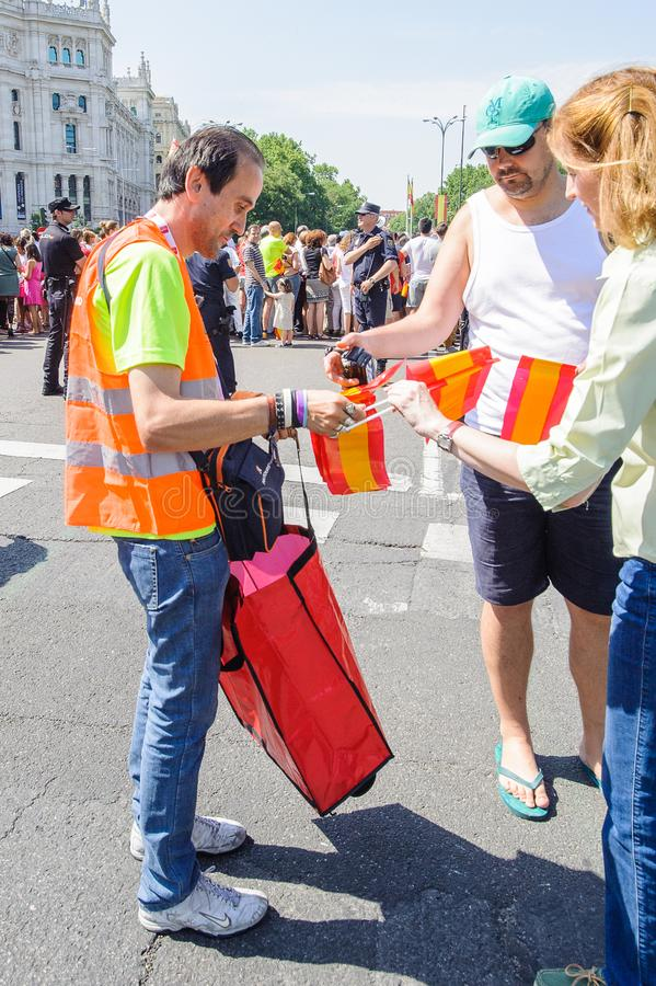 Celebration of the coronation of the New King of Spain Felipe IV. MADRID, SPAIN - JUN 19, 2014: Unidentified Spanish man sells the Spanish national flag in the royalty free stock image