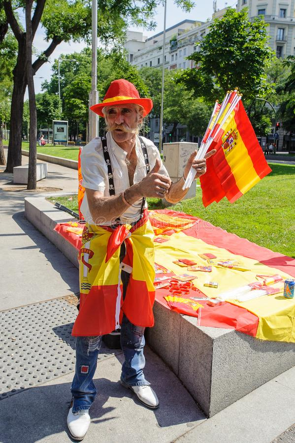 Celebration of the coronation of the New King of Spain Felipe IV. MADRID, SPAIN - JUN 19, 2014: Unidentified Spanish man sells the Spanish national flag in the royalty free stock images