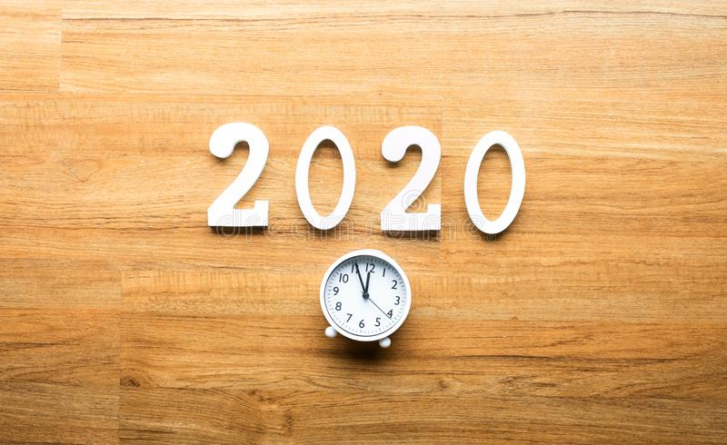 Celebration and countdown of new year 2020 concepts with text number and alarm clock on wood background. Top view royalty free stock photography
