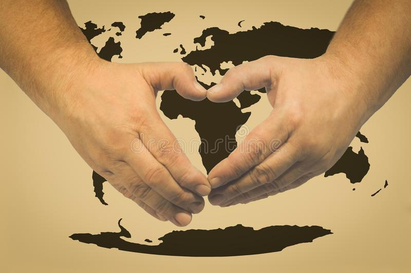 Celebration of the day of the earth - hands in the shape of a heart relating to a map of the world. Earth day concept, palms arranged in the shape of a heart on stock photo