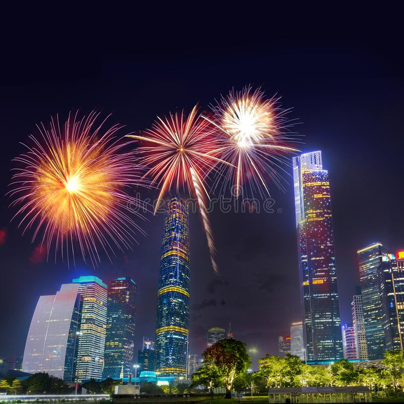Celebration firework in twilight night cityscape of guangzhou urban skyscrapers at storm with lightning  bolts in night purple. Blue sky, Guangzhou, China royalty free stock photography