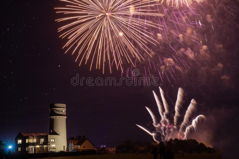 Bonfire night foreworks over lighthouse in Norfolk. Celebration fireworks display in Norfolk UK on guyfawkes night. Beautiful pyrotechnics explosion over royalty free stock images