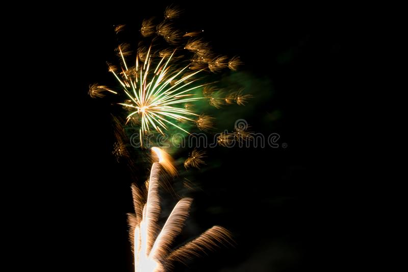 Celebration fireworks in the wind. Bright white-yellow fireworks launch train and burst with tiny blooms celebrate the occasion stock images