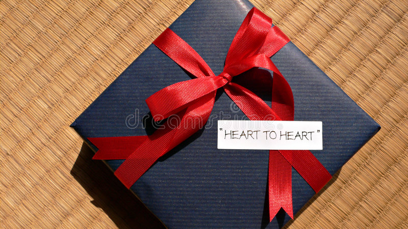 Celebration gift 'heart-to-heart'. Celebration gift with bright red bow and 'heart-to-heart' words stock images