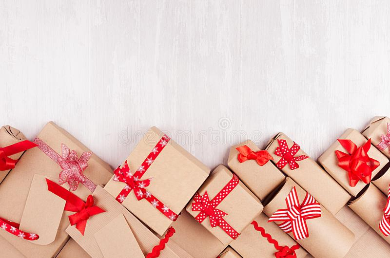 Celebration gifts background - different presents of craft paper wrapped with red ribbons and bows, blank labels on white wood. Celebration gifts background stock image