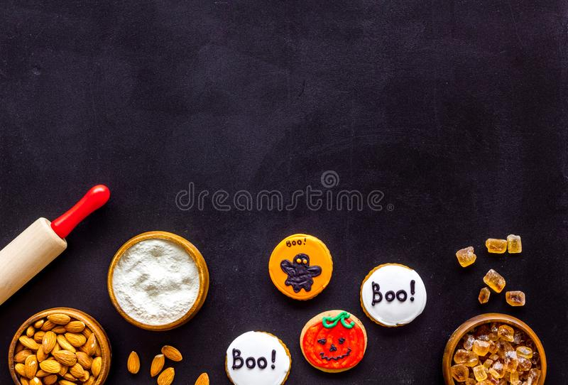 Cooking creepy cookies concept with almonds, pin, flour on black background top view mock-up. Celebration halloween and party decorations. Cooking creepy cookies stock photo