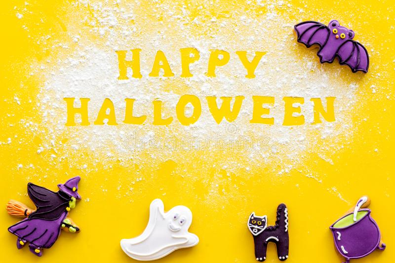 Cooking creepy cookies concept with happy halloween text written on flour on yellow background top view. Celebration halloween and party decorations. Cooking royalty free stock photos