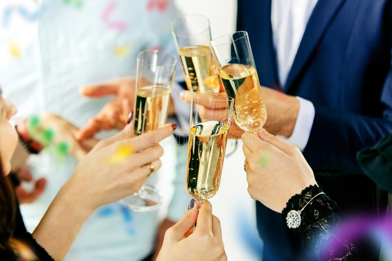 Celebration. Hands holding the glasses of champagne and wine making a toast. stock image