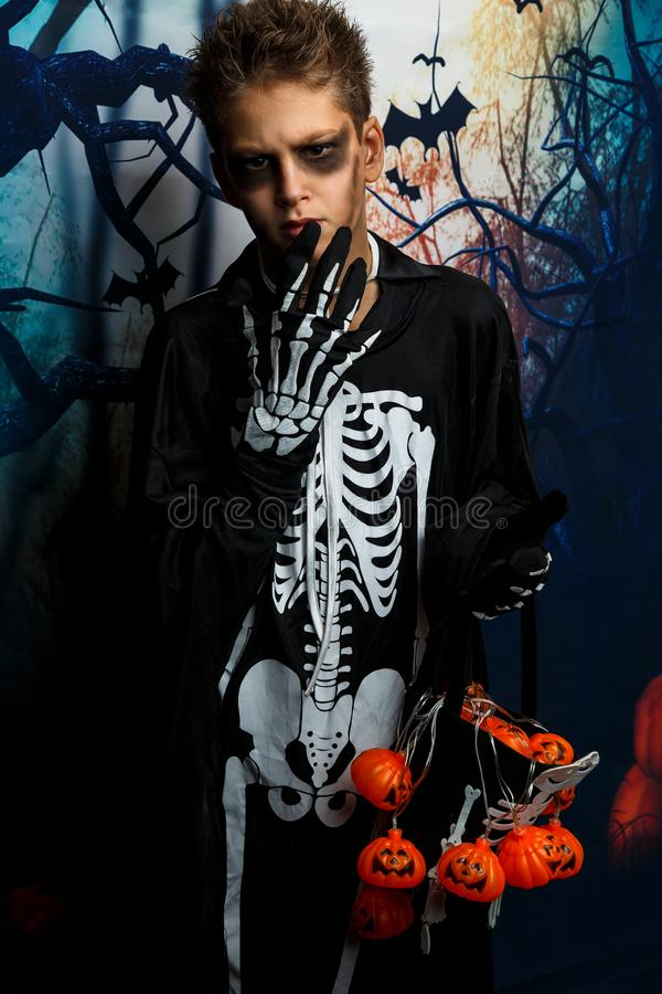 Celebration of holiday Halloween, the cute 8 year boy  in the image, costume, the skeleton theme, the vampire, bat concept stock photography