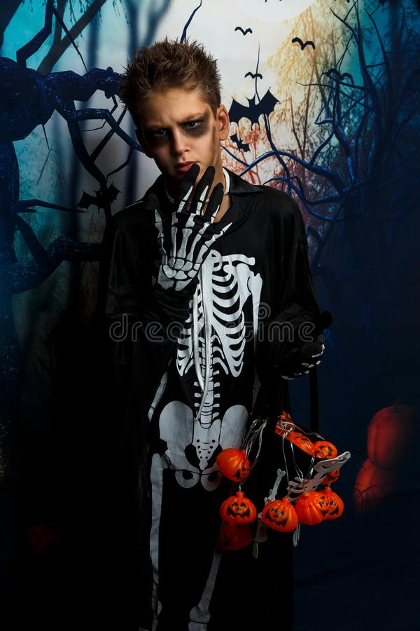 Celebration of holiday Halloween, the cute 8 year boy  in the image, costume, the skeleton theme, the vampire, bat concept royalty free stock photos