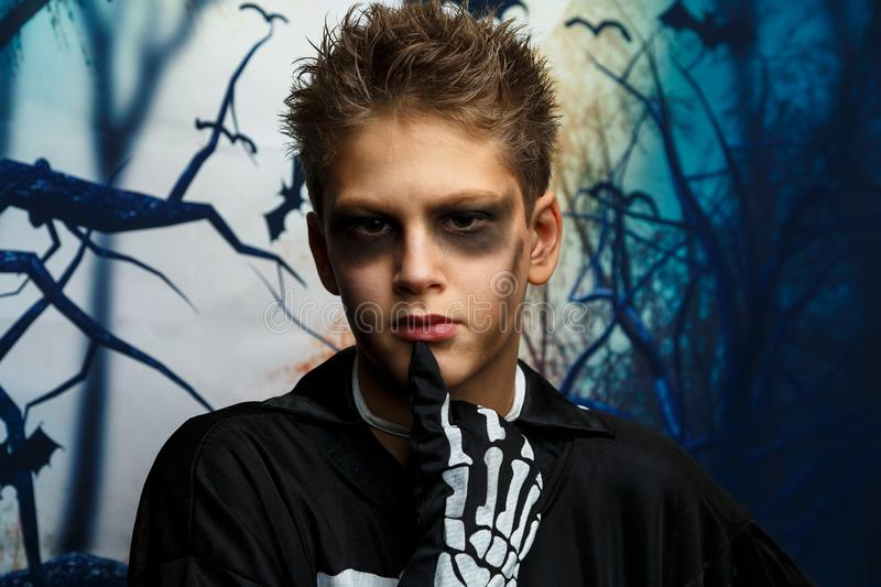 Celebration of holiday Halloween, the cute 8 year boy  in the image, costume, the skeleton theme, the vampire, bat concept. Celebration of holiday Halloween, the royalty free stock image