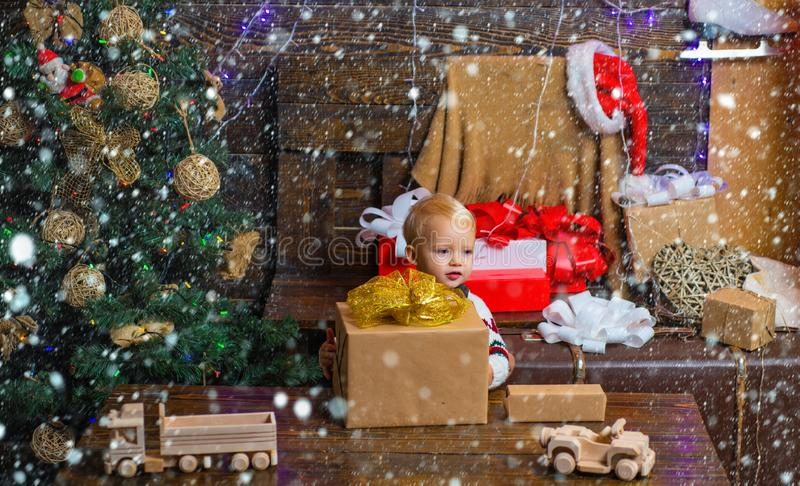 Celebration holiday. Happy small kids in santa hat with present have a christmas. Cheerful cute child opening a stock image