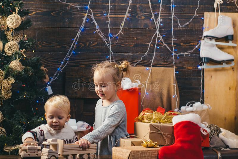 Celebration holiday. The morning before Xmas. Child with a Christmas present on wooden background. Cute little child. Near Christmas tree stock photo