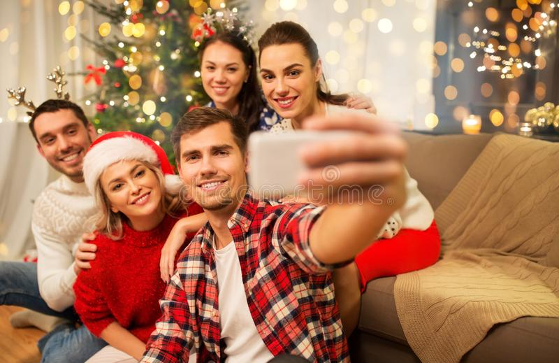 Friends celebrating christmas and taking selfie stock photography