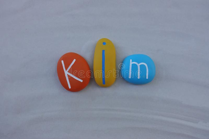 Kim, given name composed with colored stones over white sand. Celebration of Kim, given name with colored and carved stones over white sand royalty free stock photos