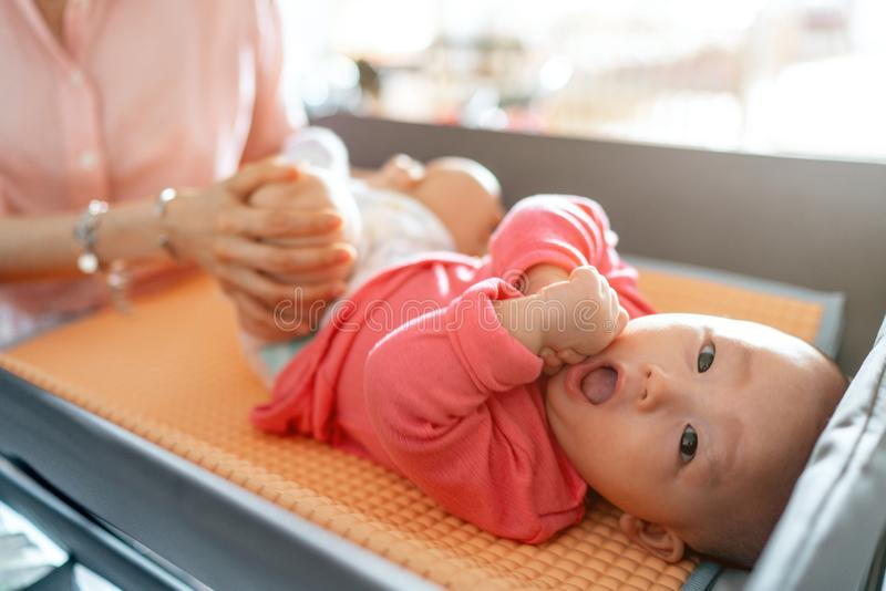 Celebration of life: cute Asian baby smiling while having diaper change royalty free stock photo