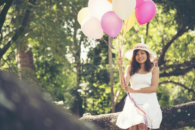 Celebration and lifestyle concept - beautiful woman with colorful balloons outdoor in the park stock photo