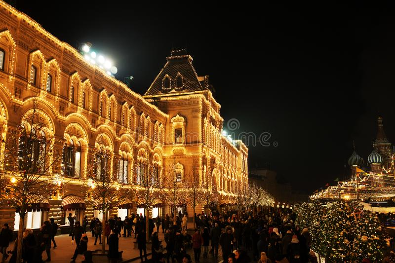 Celebration lights and decorations on Red Square for festive Christmas and New Year. Shining yellow lights on facade GUM in Moscow stock photos