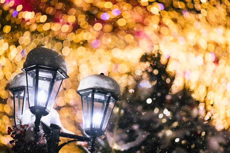 Celebration of New Year and Christmas background. Lantern lamp and Christmas tree branches with lights, snow and amazing bokeh. Outdoors stock photos