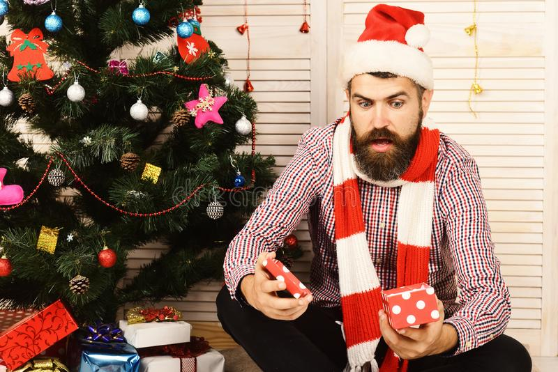 Guy in hat and scarf sits by Christmas tree. Celebration and New Year gift concept. Guy in hat and scarf sits by Christmas tree. Santa Claus with shocked face on royalty free stock images