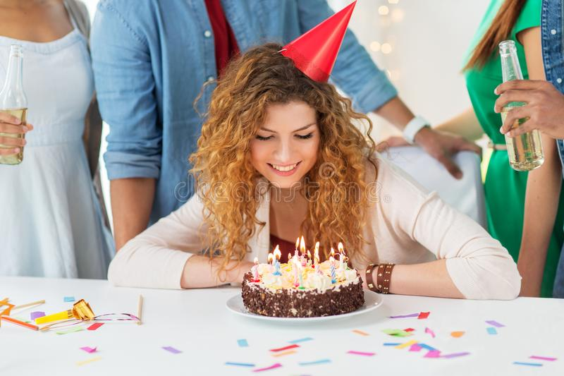 Happy woman with birthday cake at home party. Celebration and people concept - happy smiling redhead woman with candles burning on birthday cake at home party royalty free stock images