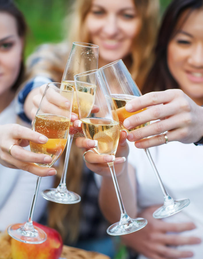 Celebration. People holding glasses of champagne making a toast. Outdoors. Summer picni royalty free stock image