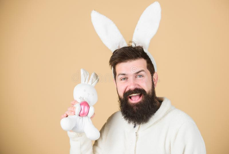 Celebration of spring time holiday. Hipster with long rabbit ears holding egg laying hare. Bearded man with bunny toy royalty free stock photos