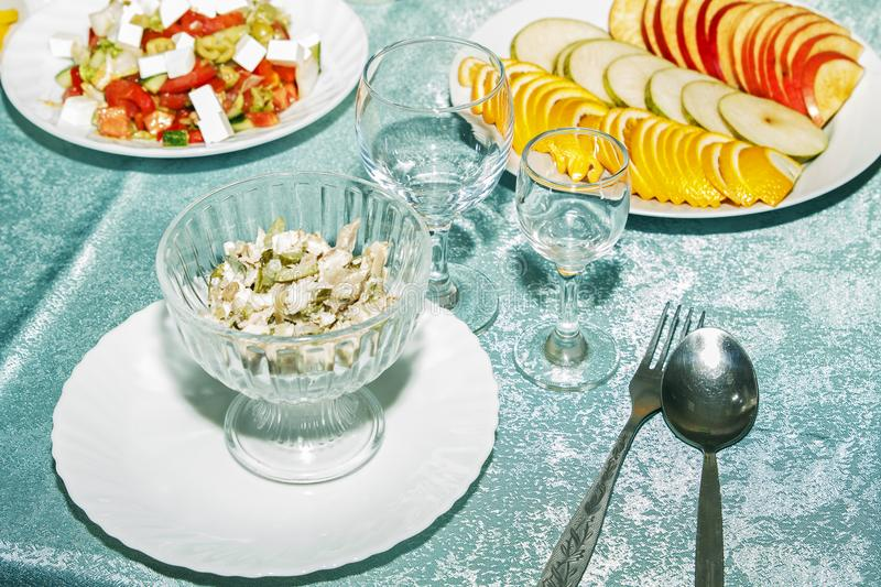 Celebration table with vegetables snack in restaurant for reception. Sliced apple, orange, pear and mushroom salad closeup. Empty. Stemware for drink and royalty free stock photos