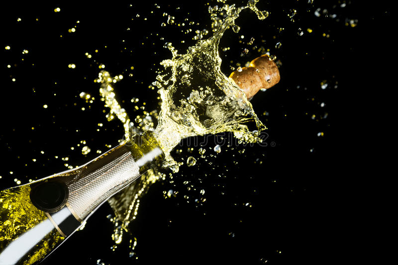 Celebration theme with explosion of splashing champagne sparkling wine on black background. stock photo