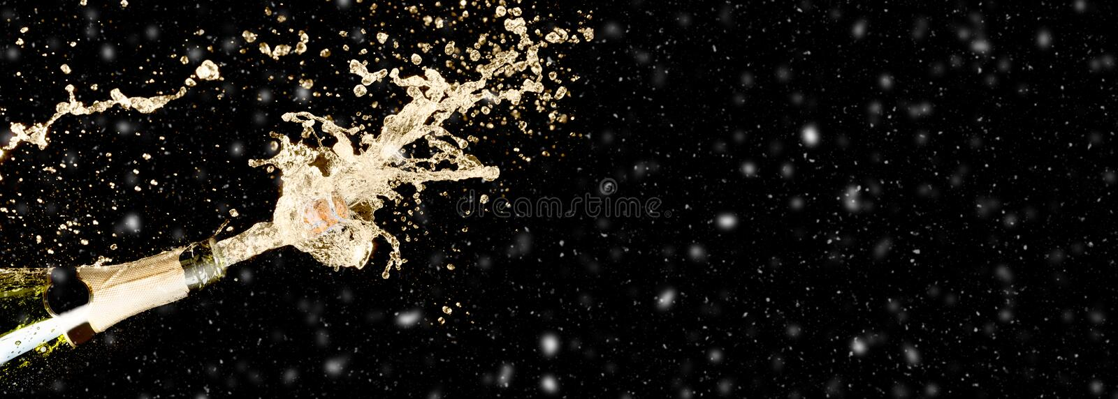 Celebration theme with splashing champagne on black background with snow and free space. Christmas or New Year, Valentines day royalty free stock image