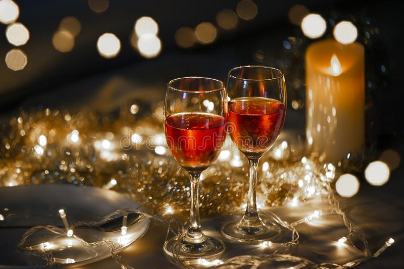 Celebration theme with  two red wine glass on  small gold light background stock photography
