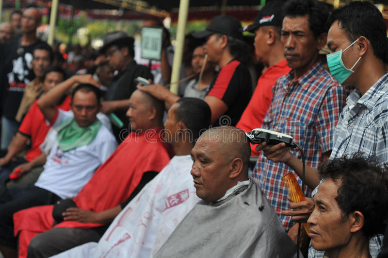 Celebration the victory of Presidential Candidate Joko Widodo. Supporters shave hair to bald to celebrate the victory of Presidential Candidate Joko Widodo in stock photography