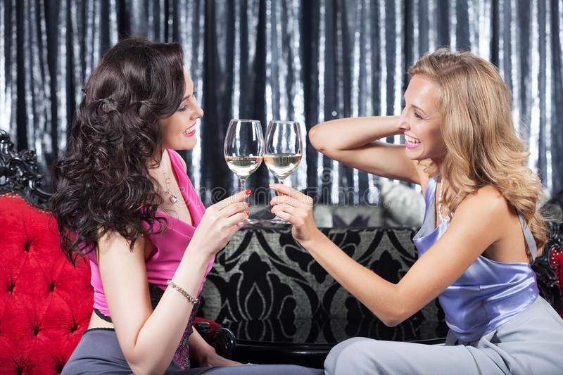 Celebration with wine. Two elegant happy girls in the restaurant drinking wine royalty free stock image