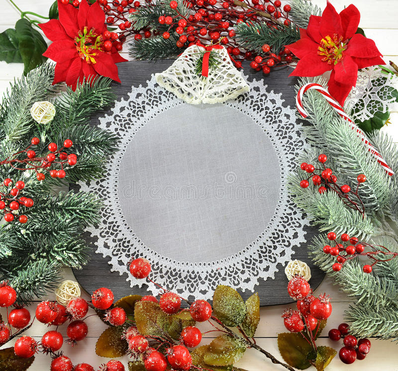 Celebratory border with napkin and Christmas decorations. Christmas and New Year border in form of plate with white round napkin, conifer, poinsettia flowers and stock image