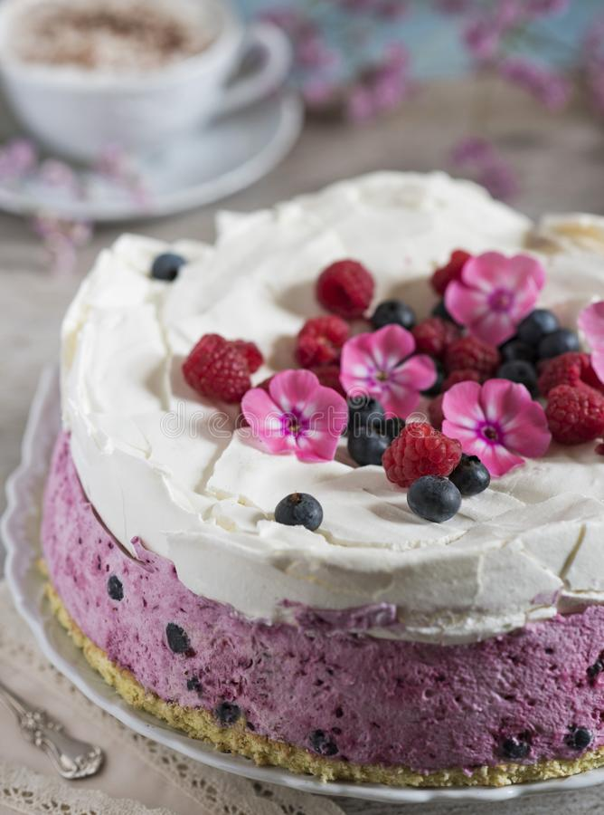 Celebratory cake with berries and a cup of aromatic coffee. Vintage napkin, spoon and pink flowers royalty free stock photo