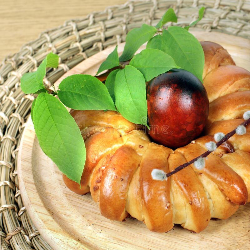 Celebratory Easter bread and eggs. Celebratory Easter bread decoration color eggs and green leaves royalty free stock photography