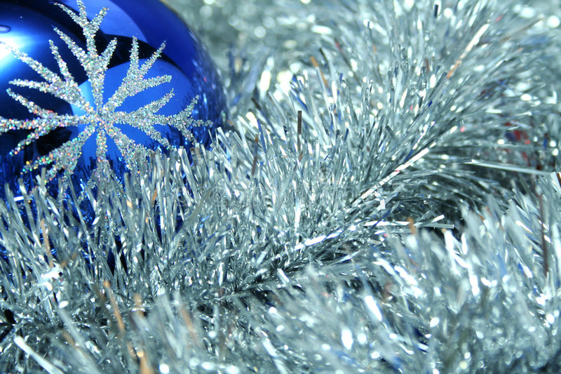 Celebratory glass sphere of dark blue color 5. Celebratory glass sphere of dark blue color with a pattern on a background of a silvery New Year's tinsel royalty free stock image