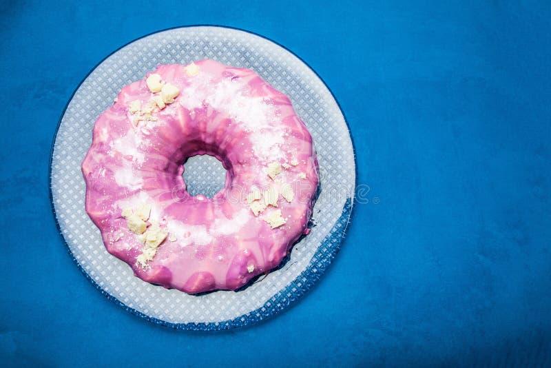 Celebratory rund kaka med rosa isläggning på en blå bakgrund arkivfoto