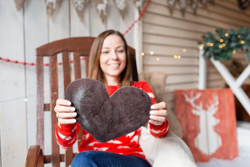 Celebrazione del nuovo anno o di Natale Donna felice che si siede nella sedia di oscillazione Tenuta della figura del cuore da le fotografia stock libera da diritti