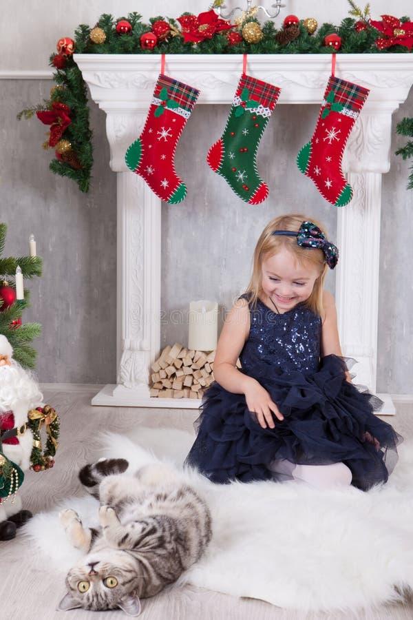 Celebrazione del nuovo anno o di Natale Feste felici Bambina che gioca con il gatto vicino all'albero di Natale ed il camino con  immagine stock