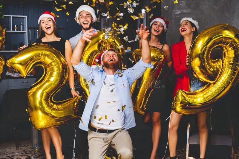 Celebrazione del partito del nuovo anno Il gruppo di ragazze allegre in bello oro di trasporto d'uso ha colorato i numeri 2019 e fotografie stock