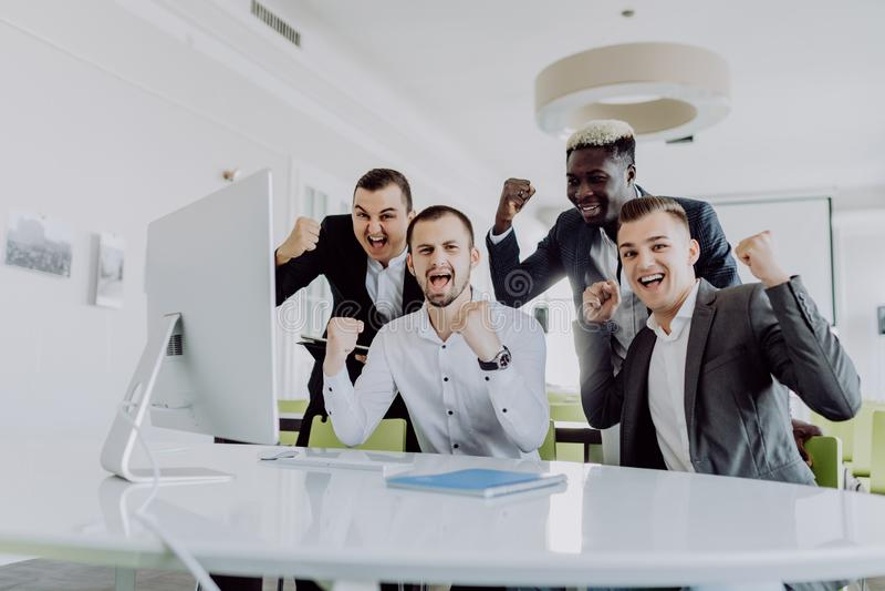 Celebrazione del successo Gruppo di gente di affari che alza le loro armi e che sembra felice mentre sedendosi intorno allo scrit fotografia stock