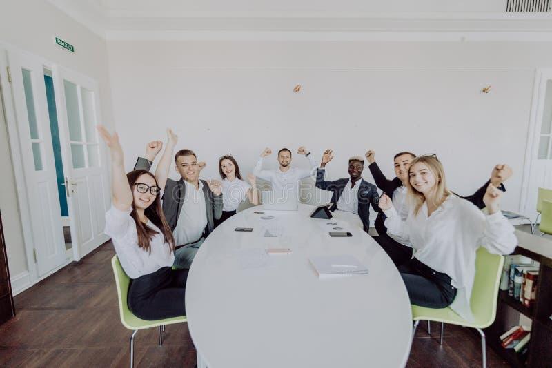 Celebrazione del successo Gruppo di gente di affari che alza le loro armi e che sembra felice mentre sedendosi intorno allo scrit immagine stock