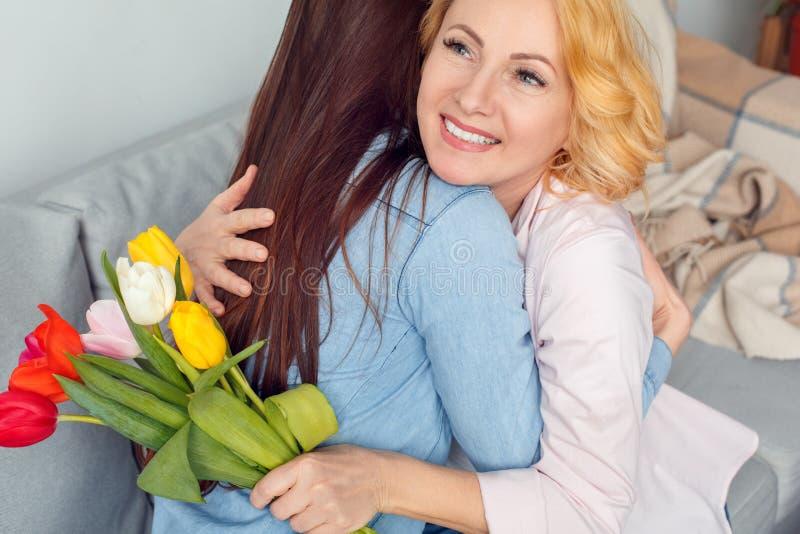 Celebrazione della figlia e della madre insieme a casa che si siede con abbracciare dei tulipani allegro immagine stock libera da diritti