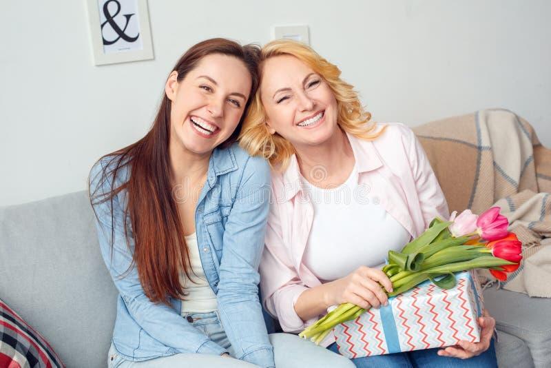 Celebrazione della figlia e della madre insieme a casa che si siede con il presente ed i fiori che guardano risata della macchina fotografie stock libere da diritti