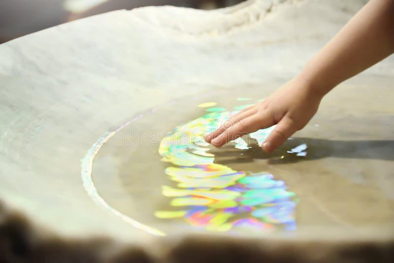 Celebrazione di battesimo Mucchio battesimale e una mano con acqua sacra in una chiesa spazio vuoto della copia fotografia stock libera da diritti