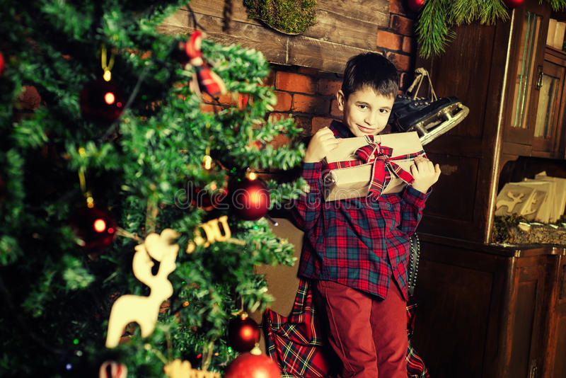 Celebrazione di famiglia del nuovo anno Ragazzo vicino all'albero di Natale immagine stock libera da diritti