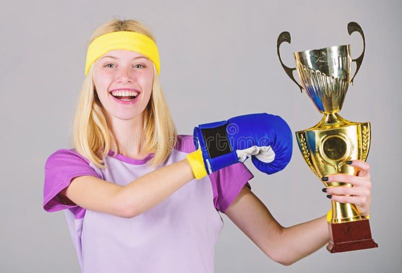 Celebri la vittoria Campione di pugilato Guantone da pugile atletico della ragazza e calice dorato Attrezzatura di sport di usura fotografia stock